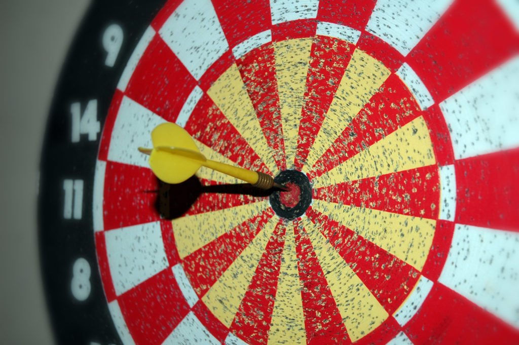 black, red and white dart board with yellow dart stuck in the middle